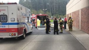 Emergency personnel gather outside the Coos Bay Hospital in Oregon after a mass hallucination episode